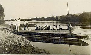 Fran Vesel - Skupina ljudi v čolnu in na obali pozira ob reki.jpg