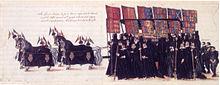 Quatre chevaux avec une couverture noire tirent un cerceuil où se trouve la dépouille de la reine portant une robe dorée. L'attelage est entouré de personnages portant de longs manteaux noirs à capuche qui tiennent des bannières avec les armoiries de l'Angleterre à diverses périodes