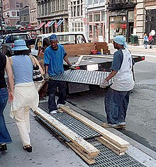 Two people in work gloves carefully transferring a heavy panel of pavement lights from a small flat-bed truck to a pile of similar panels, separated by wooden spacers. The pile is on the outside edge of the sidewalk, and pedestrians pass them on the inside. The panel has a black metal frame and round white lenses. It is about 1.5x0.5m (possibly 2x4 feet)