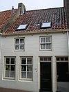 foto van Gebosseerd gepleisterd pand met verdieping onder zadeldak gedekt met rode hollandse pannen, zesruitsschuifvensters op de begane grond, vierruits op verdieping; deur met bovenlicht; goot op geprofileerde klossen