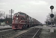 A red electric locomotive approaches the viewer from the left lane in a right-hand-drive context, opposite of the viewer. A telephone pole, stop sign, and railroad crossing can be seen in the distance.