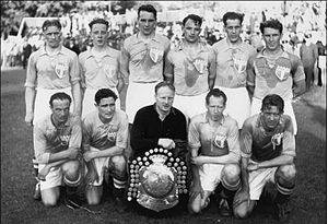 An association football team poses for a formative black-and-white photograph. A row of five men are kneeling on the pitch, all wearing light-coloured shirts and white shorts apart from the player in the centre, who wears black. In front of him is a large trophy shield. Behind the kneeling row stand six more men, all wearing the same light-coloured shirts. The players are noticeably tired; large sweat stains are visible on their shirts. A stand of a stadium can be seen in the background.