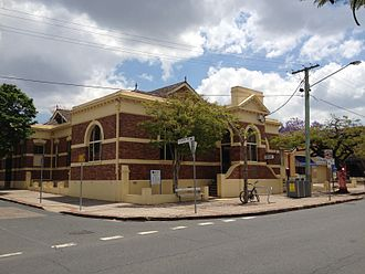 Racecourse Road, Brisbane - Old Hamilton Town Hall, now a city library, seen from Racecourse Road. A poincinia tree decorated by the Pink Poincinia Project can be seen at the right.