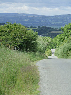 A country road in a hilly Irish landscape
