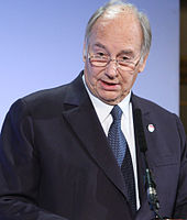 The Aga Khan giving a speech into a microphone