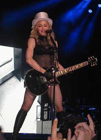 "Human Nature (Madonna song) - Madonna performing ""Human Nature"" on the Sticky & Sweet Tour (2008–2009), while playing a black Les Paul guitar"