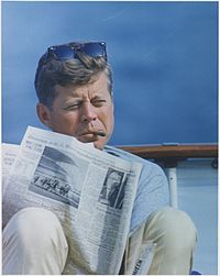 "Hyannisport Weekend. President Kennedy with cigar and New York Times. Hyannisport, MA, aboard the ""Honey Fitz"". - NARA - 194268.jpg"