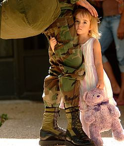 A little girl in a white dress holds on to a pink teddy bear in one hand and the leg of her father with the other. The father's face is not seen and he wears green and brown military fatigues and has a green bag over his shoulder.