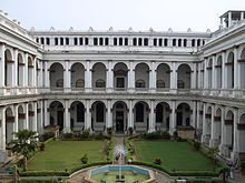 A white two storied building with arches and a courtyard in the foreground