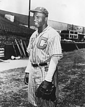 "A black man in baseball uniform with the letters ""K"" and ""C"" on the chest"