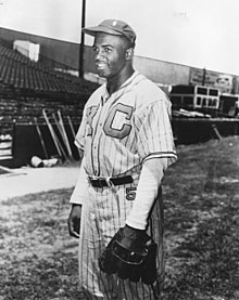 An African-American man wearing a pinstriped baseball uniform, hat, and glove