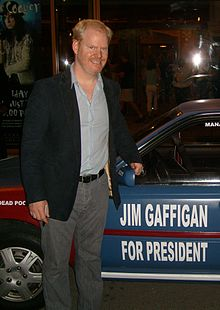 "Gaffigan standing next to a car reading ""JIM GAFFIGAN / FOR PRESIDENT"""