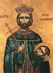 Religious painting of a man in his thirties with a short beard and mustache, wearing a crown and regal robe, holding a cross in his right hand and a severed human head in his left hand.