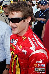 A man in his late twenties wearing black sunglasses with a head full of hair and a red jacket with sponsors' logos.