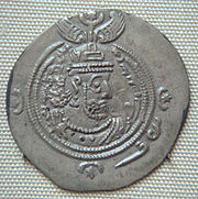 A silver coin with a face of Khosrau II surrounded by a double ring and some symbols