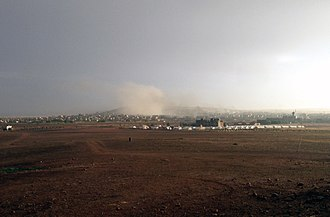 Kobanî - Kobani during the bombardment of ISIL targets by US-led forces. Photo taken from Turkish-Syrian border at Suruç,Suruc, Turkey showing refugee camp in the middle distance (October 2014)