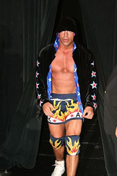 Adult white male wearing wrestling tights and knee pads as well as a black jacket.