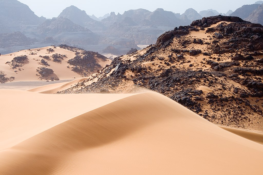 Bukit pasir, bebatuan, dan pegunungan di Tadrart Acacus, daerah gurun di Libya barat daya, bagian dari Sahara