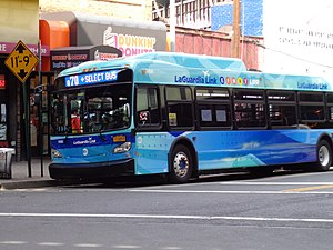 A Q70 SBS bus in LaGuardia Link livery, stopping in Woodside, Queens
