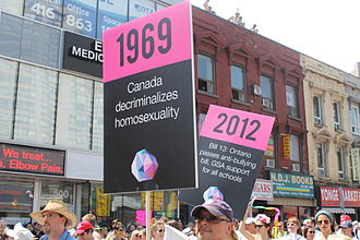 InterPride - Marchers at Pride Toronto 2014 with signs commemorating significant events in LGBT history in Canada. In 2014, Toronto hosted WorldPride.