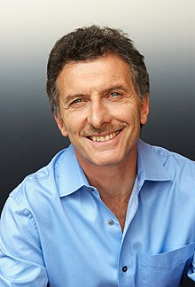 A smiling Macri in a light-blue shirt