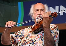 Michael Doucet playing the fiddle with the bow in his right hand. He has white hair.