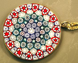 "Caneworking - A small (1 ½"") disc of millefiori-patterned glass.  Each of the stars or flowers is a cross-section of a cane"