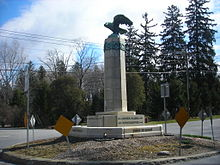 A tall monument sits in the center of an intersection. At the base are the names of nearby locations as well as arrows denoting where the locations are in respect to this intersection.
