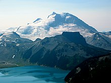 Prominent mountain rising over a smaller steep-sided, flat-topped mountain and a turquoise-coloured alpine lake.