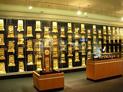 A room with glass display cases containing rectangular, wooden trophies that are gold-plated.