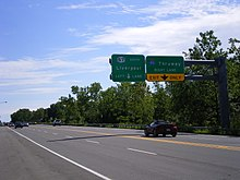 Overhead sign on a four-lane road with a New York state route marker instead of the pentagonal county shield