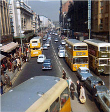 A busy urban street in Newcastle in the late 1960s. There are tall buildings on either side of the street, and various 1960s cars and buses on the road.