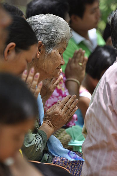 elderly woman in crowd prays