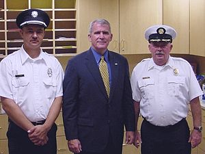 Oliver North - Oliver North in 2005, pictured with Clinton Township, Franklin County, Ohio Assistant Fire Chief John Harris and Lieutenant Douglas Brown, at a public speaking event.