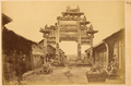 Ornamental Gateway (Pailou) from Han Dynasty (202 BCE – 220 CE) across a Street Lined with Small Shops. Hanzhong, Shaanxi Province, China, 1875 WDL2092.png