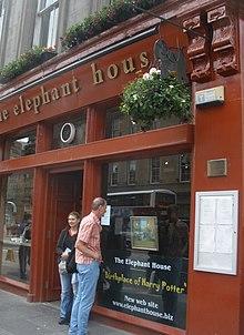 La devanture rouge vif d'un pub où l'auteure a rédigé Harry Potter : sur la vitrine est écrit en lettres dorées et en anglais « Lieu de naissance de Harry Potter »
