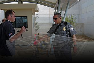 A USPPD policeman checks a man's identification card at the Pentagon in the early 2010s. Pentagon Force Protection Agency policeman checks a man's ID card.jpg