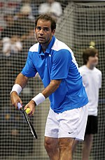 A man, with a modern racket in his right hand and a tennis ball in his left hand, prepares to serve