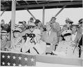 Photograph of President Truman peering through binoculars, with other dignitaries, watching war games involving... - NARA - 200216.tif
