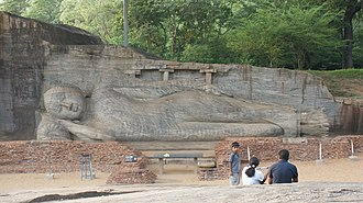 Rock relief - Reclining Buddha at Gal Vihara, Sri Lanka.  The remains of the image house that originally enclosed it can be seen.