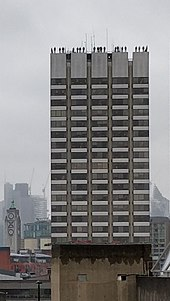 A photograph of the Project84 installation in London. A tall tower block - at the apex, statues of men stand disturbingly close to the edge.