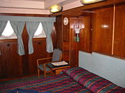 First Class accommodations on the Queen Mary, converted into a present-day hotel room with modern curtains, bedding and amenities surrounded by original wood paneling, portholes and light fixtures.