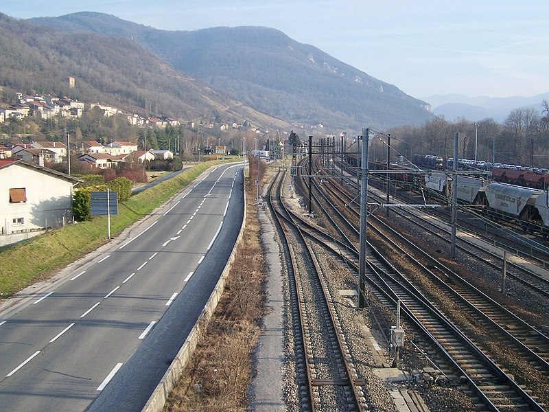 Sight of French RD 1504 road and Lyon to Geneva (Switzerland) railway line leaving city of Ambérieu-en-Bugey in Ain and goint to the Alps.