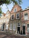 foto van Gepleisterde lijstgevel voor huis van parterre en verdieping met schilddak. Stoep met stoeppalen
