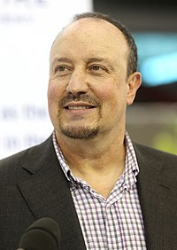 Rafael Benitez is seen with a beard while wearing a coat over a buttoned-up shirt.