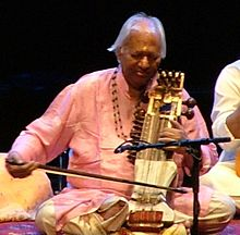 An old man sits cross-legged on a platform and plays a bowed instrument.