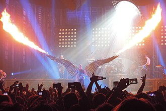 """Till Lindemann - Lindemann at a Rammstein concert during a performance of """"Engel"""", wearing angel wings fitted with flamethrowers"""