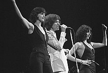 Three people stand onstage next to each other singing. The man in the middle wears white clothes and on either side is a woman wearing black.