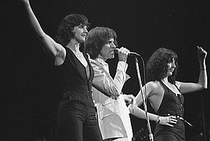 Arena rock - British rocker Ray Davies performs with his backup singers at the Canadian venue Maple Leaf Gardens in April 1977; his band, The Kinks, is an example of an older rock and roll group that adapted to an arena rock sound.