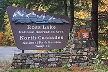 """Outdoor sign with an image of mountain, the National Park Service logo, and the words """"Ross Lake National Recreation Area, North Cascades National Park Service Complex"""""""